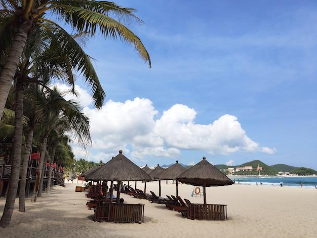 Belle vue sur la plage tropicale de dadonheis avec ses parasols en chaume abrite des maisons en chine sur l'île de hainan en traîneau avec l'océan et le sable jusqu'à la plage