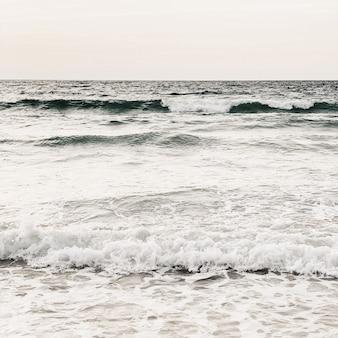 Belle vue sur la plage tropicale avec sable blanc, mer beige avec vagues et ciel clair sur phuket