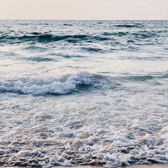 Belle vue sur la plage tropicale avec sable blanc, mer bleue avec vagues et ciel clair sur phuket
