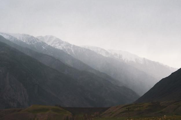 Belle vue sur les silhouettes des montagnes de l'altaï par temps de pluie et de brouillard