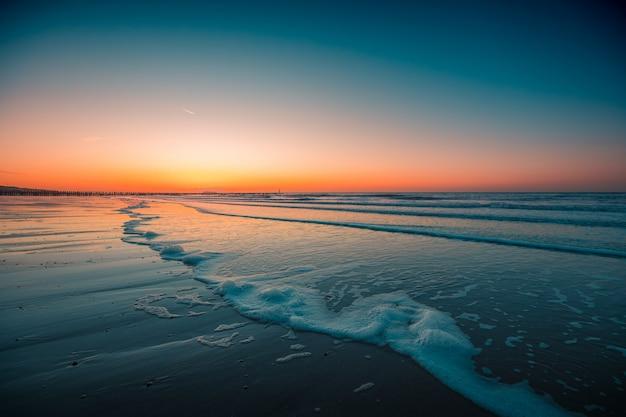 Belle vue sur les vagues mousseuses sur la plage sous le coucher du soleil capturé à domburg, pays-bas