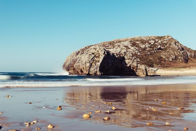 Belle vue sur les vagues se brisant sur les rochers près de la plage par temps clair