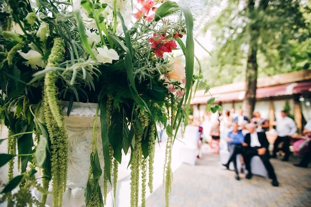 Belle zone photo de mariage dans le parc à l'ombre, un écran blanc, un piédestal avec des fleurs et un décor.