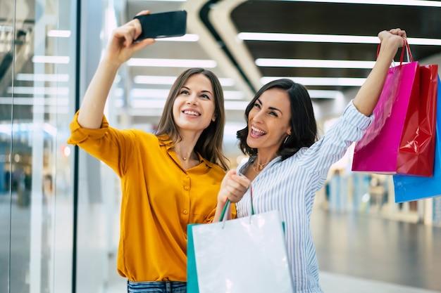 Belles amies de jeune fille heureuse et excitée avec des sacs en papier et un téléphone intelligent se promènent dans le centre commercial