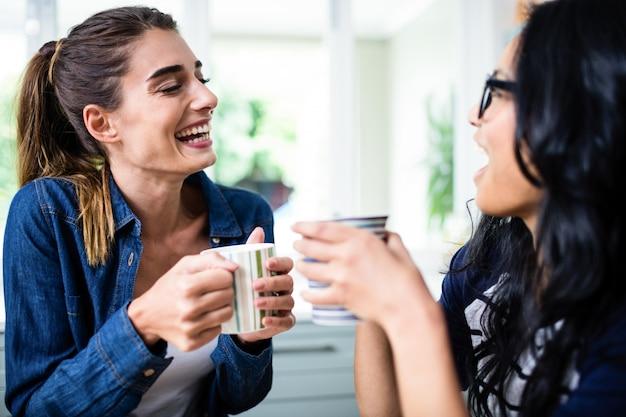 Belles amies rire en buvant du café