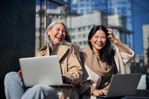 Belles amies utilisant des ordinateurs portables et riant