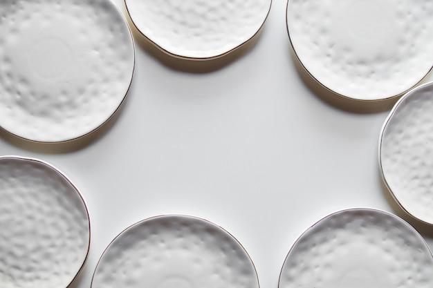 Belles assiettes sur fond blanc avec du coton. belle mise en page