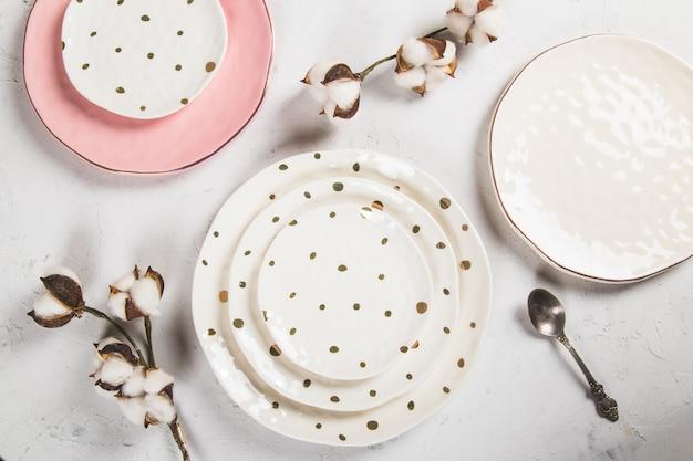 Belles assiettes sur fond blanc avec plante séchée