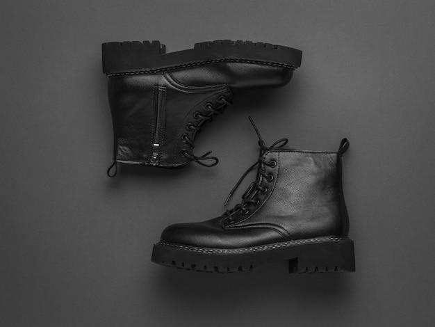 Belles bottes hautes en cuir à lacets sur une surface sombre