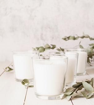 Belles bougies allumées blanches avec des feuilles d'eucalyptus sur une surface en bois blanche