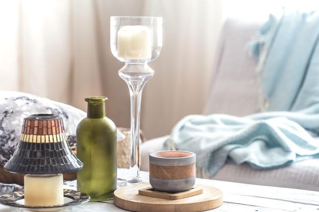 Belles bougies allumées avec des bouteilles sur un tableau blanc