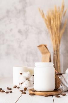 Belles bougies allumées avec des fleurs de coton et des grains de café sur une surface en bois blanche