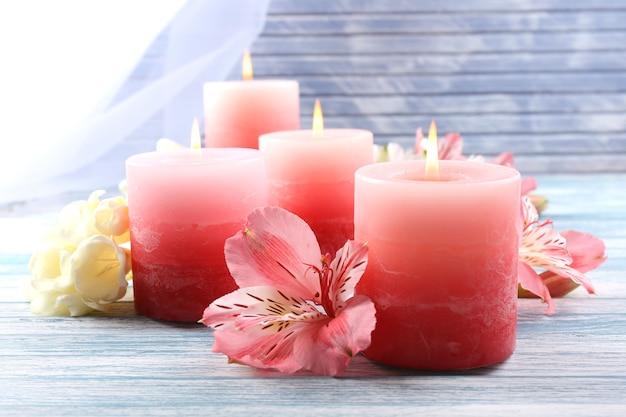 Belles bougies avec des fleurs sur une surface en bois