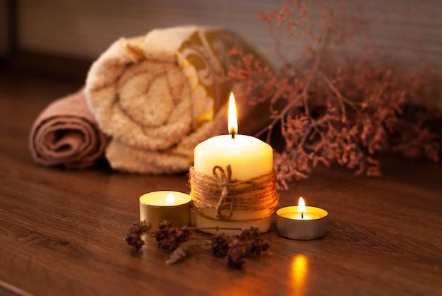 Belles bougies à la vanille crème jaune clair brûlant avec une flamme vive et des serviettes de couleur naturelle