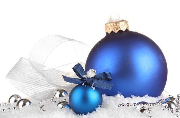 Belles boules de noël bleues sur la neige, isolées sur blanc