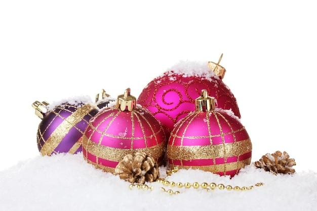 Belles boules de noël roses et cônes sur neige isolé sur blanc