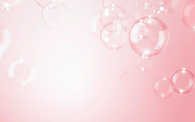 Belles bulles de savon transparent brillant fond rose.