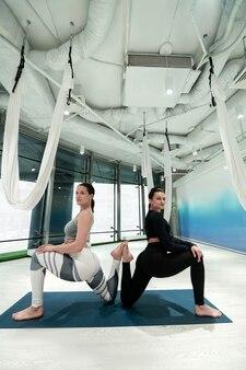 Belles carrosseries sportives. femmes minces aux cheveux noirs avec de beaux corps sportifs pratiquant le yoga ensemble