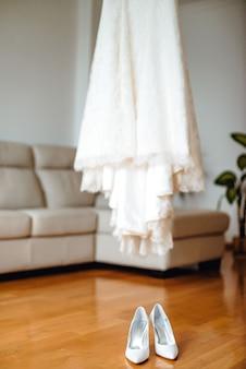 Belles chaussures de mariage et robe sur un sol en bois marron