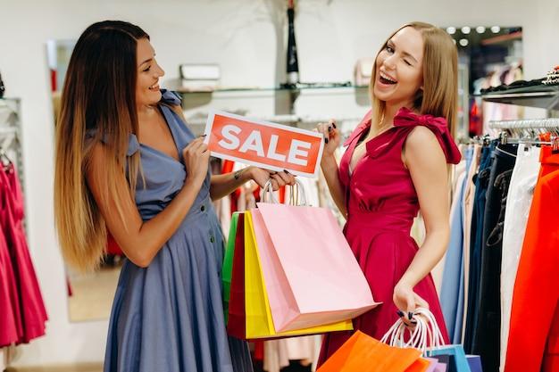 Belles copines dans les magasins ont acheté des vêtements à prix réduit