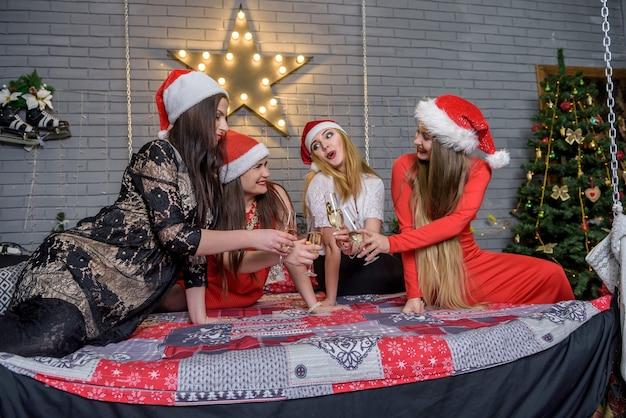 Belles dames avec des verres à champagne assis près de l'arbre de noël