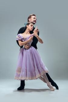 Belles danseurs de salle de bal contemporains isolés sur mur gris studio