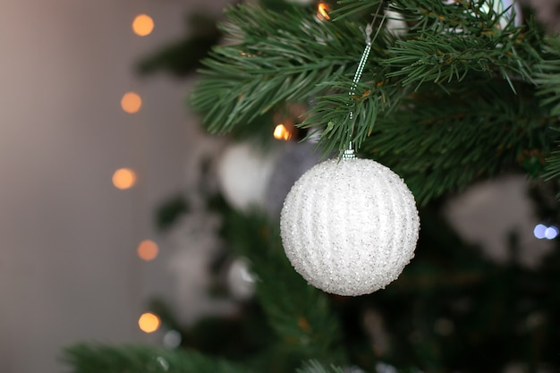 Belles décorations de noël suspendues sur l'arbre de noël. photo macro de boule de noël blanche et guirlande lumineuse sur l'arbre de noël.