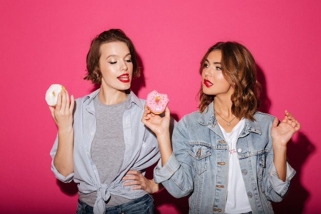 Belles deux femmes amis manger des beignets