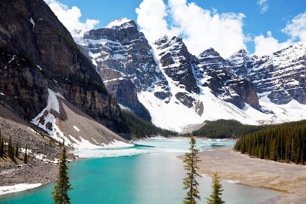 Belles eaux turquoise du lac moraine avec des pics enneigés au-dessus dans le parc national du canada banff