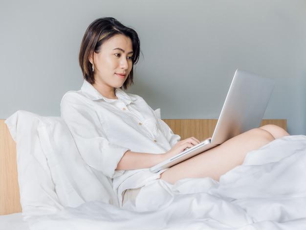Belles femmes asiatiques aux cheveux courts portant une chemise blanche travaillant avec un ordinateur portable sur le lit dans la maison.