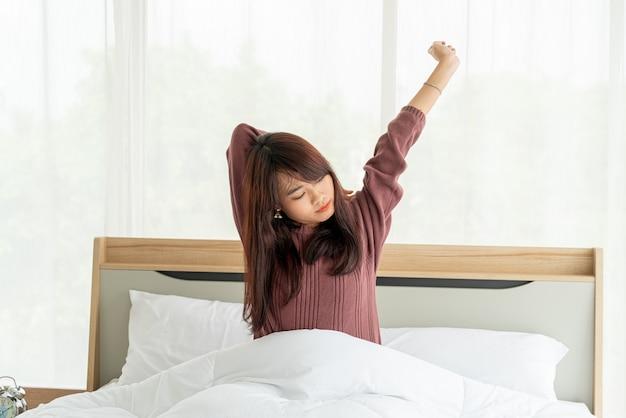 Belles femmes asiatiques sur le lit et se réveiller le matin