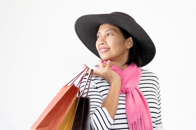 Belles femmes asiatiques portant des chapeaux noirs et une écharpe rose souriante et heureuse, portant de nombreux sacs à provisions.