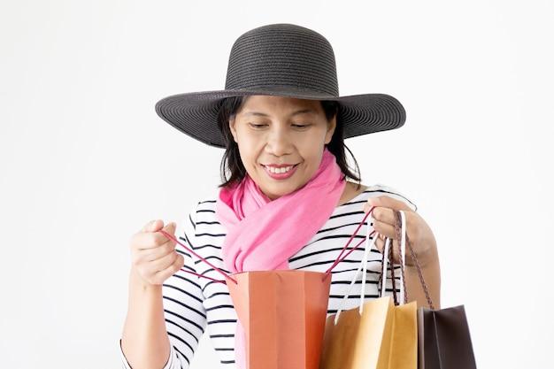 Belles femmes asiatiques portant des chapeaux noirs et une écharpe rose souriante et heureuse, à la recherche de ses sacs à provisions.
