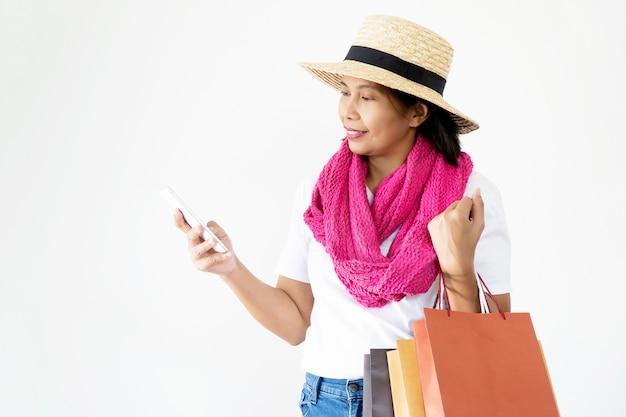 Belles femmes asiatiques portant des chapeaux de paille souriants et heureux, portant de nombreux sacs à provisions et téléphones portables.