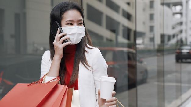 Belles femmes asiatiques avec des sacs à provisions dans la ville