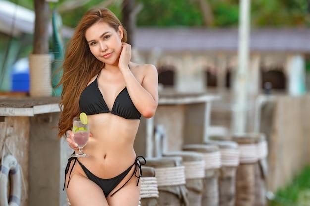Belles femmes asiatiques ou thaïlandaises et bikinis noirs au bar, se détendre à la plage pour voyager dans le concept d'été