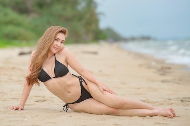 Belles femmes asiatiques ou thaïlandaises et bikinis noirs à la plage, se détendre à la plage pour voyager dans le concept d'été