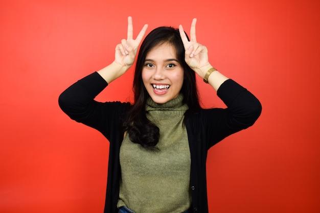 Belles femmes asiatiques utilisant des doigts de pull noir sur la tête comme des oreilles de lapin avec un fond isolé rouge