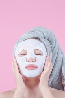 De belles femmes asiatiques utilisent un masque sur une feuille sur un fond rose.