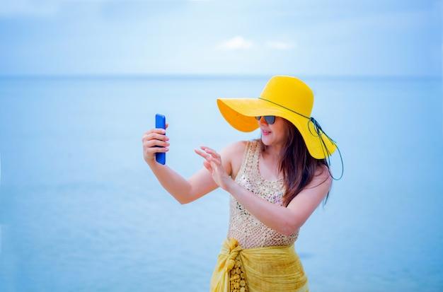De belles femmes asiatiques voyagent à la plage en été. soleil de sable de mer. concept de vacances et de vacances. utiliser un téléphone intelligent pour la photo de tâche