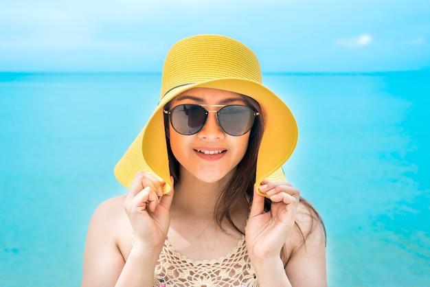 De belles femmes asiatiques voyagent à la plage en été. soleil de sable de mer et vacances.