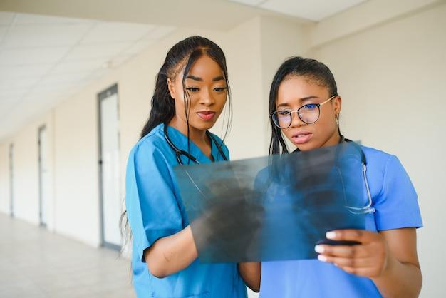 De belles femmes et de beaux médecins afro-américains examinent une photographie aux rayons x, deux autres médecins parlent en arrière-plan