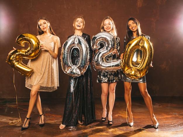 Belles femmes célébrant le nouvel an. heureuses filles magnifiques dans des robes de soirée sexy élégantes tenant des ballons d'or et d'argent 2020, s'amusant à la fête du nouvel an. célébration des fêtes modèles charmants