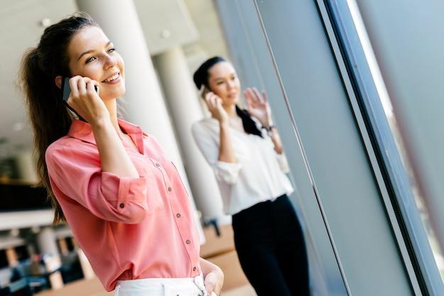 Belles femmes, collègues utilisant des téléphones et parlant pendant la pause