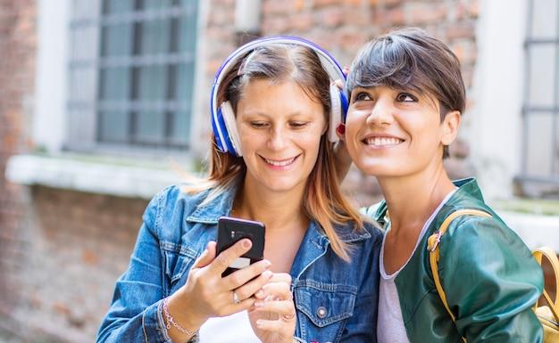 De belles femmes écoutent de la musique avec un casque sur le téléphone
