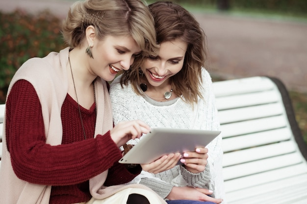 Belles femmes filles automne avec tablette en plein air