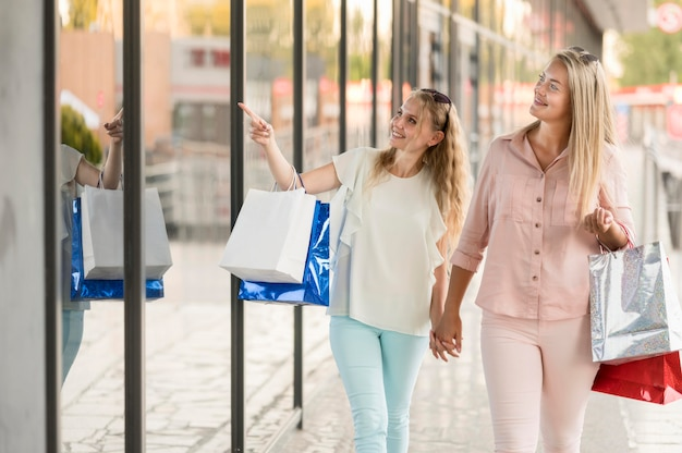 Belles femmes heureuses de faire du shopping ensemble