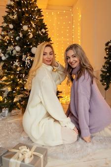 De belles femmes heureuses en vêtements tricotés avec un pull vintage s'assoient près de l'arbre de noël avec des cadeaux. bruyant