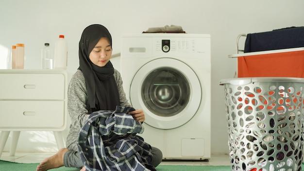 De belles femmes en hijab laveront les vêtements à la maison