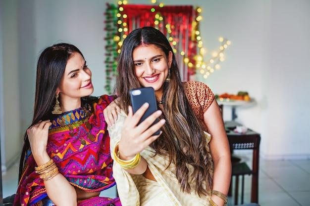 Belles femmes indiennes prenant selfie dans une chambre décorée